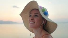 Mujer atractiva que canta mientras que música que escucha en los auriculares metrajes