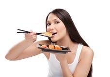 Mujer atractiva que come el sushi con palillos Fotografía de archivo