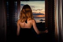 Mujer atractiva que considera hacia fuera puertas francesas la puesta del sol Foto de archivo libre de regalías