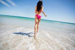 Mujer atractiva que corre en la playa Imagenes de archivo