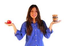 Mujer atractiva que decide comer la manzana o el buñuelo Fotografía de archivo
