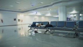Mujer atractiva que duerme en la zona de espera del aeropuerto almacen de metraje de vídeo