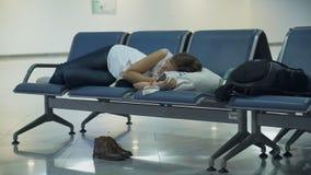 Mujer atractiva que duerme en la zona de espera del aeropuerto metrajes