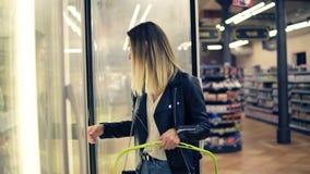 Mujer atractiva que elige los productos lácteos en el supermercado en refrigerador La mujer joven lleva productos congelados a almacen de video