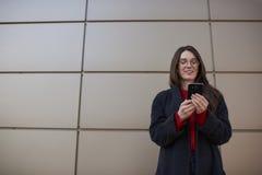 Mujer atractiva que envía SMS vía el smartphone moderno que se coloca en urbano Foto de archivo