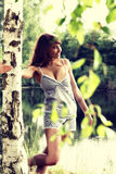 Mujer atractiva que goza del sol de la mañana en el parque Imagenes de archivo