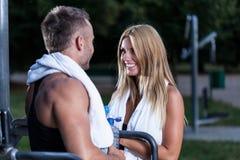 Mujer atractiva que habla con el hombre atlético Imágenes de archivo libres de regalías
