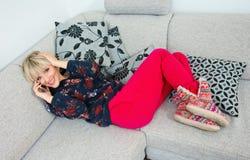 Mujer atractiva que habla con el teléfono en el sofá Fotografía de archivo libre de regalías