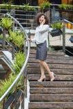 Mujer atractiva que habla en el teléfono que se coloca en las escaleras Imagenes de archivo