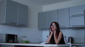 Mujer atractiva que habla en el teléfono que se sienta en casa, sonriendo y riendo metrajes