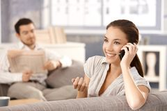 Mujer atractiva que habla en la sonrisa del teléfono Imagen de archivo libre de regalías