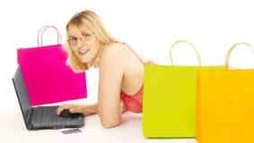 Mujer atractiva que hace compras sobre el Internet Imágenes de archivo libres de regalías