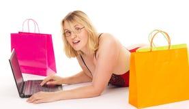 Mujer atractiva que hace compras sobre el Internet Foto de archivo libre de regalías