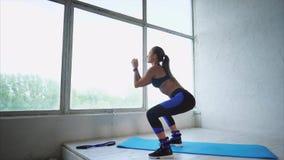Mujer atractiva que hace ejercicios en los músculos de nalgas en club de deportes metrajes