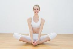 Mujer atractiva que hace la actitud de la yoga que se sienta en la posición de loto en pasillo de deportes Imagenes de archivo