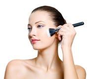 Mujer atractiva que hace maquillaje Imagenes de archivo