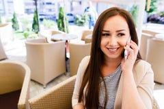 Mujer atractiva que hace una llamada de teléfono mientras que pasa tiempo en descanso para tomar café Fotos de archivo
