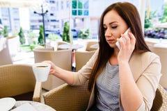 Mujer atractiva que hace una llamada de teléfono mientras que pasa tiempo en descanso para tomar café Fotos de archivo libres de regalías