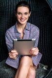 Mujer atractiva que hojea en el dispositivo de almohadilla táctil Foto de archivo