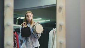 Mujer atractiva que intenta en los bolsos delante de un espejo en un boutique metrajes
