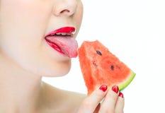 Mujer atractiva que lame la sandía con los labios rojos, deseo Imagen de archivo