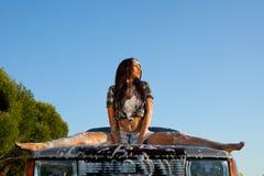 Mujer atractiva que lava un coche en la puesta del sol imagen de archivo libre de regalías