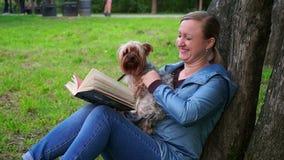 Mujer atractiva que lee un libro en un parque por el árbol Un perro lindo corre a ella, slowmo almacen de video