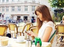 Mujer atractiva que lee un mensaje de texto fotografía de archivo