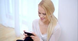 Mujer atractiva que lee un mensaje en su teléfono almacen de metraje de vídeo