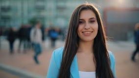 Mujer atractiva que liga en una c?mara que camina en cuadrado de ciudad almacen de video