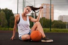 Mujer atractiva que lleva a cabo baloncesto disponible Fotografía de archivo libre de regalías