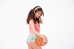 Mujer atractiva que lleva a cabo la bola del baloncesto y la música que escucha en auriculares Fotografía de archivo libre de regalías