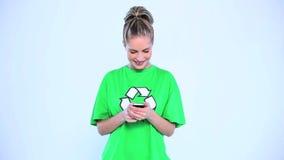 Mujer atractiva que lleva una camiseta verde con el reciclaje de símbolo en él almacen de video