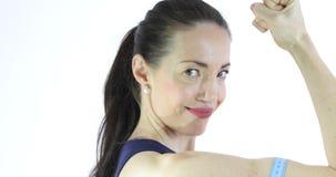 Mujer atractiva que mide su bíceps del entrenamiento almacen de metraje de vídeo