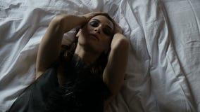 Mujer atractiva que miente en cama metrajes
