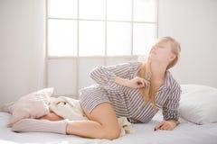 Mujer atractiva que miente en cama y que juega con su pelo Fotos de archivo