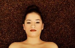 Mujer atractiva que miente en granos de café Imagen de archivo