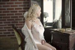 Mujer atractiva que mira en un espejo de vanidad Fotografía de archivo