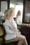 Mujer atractiva que mira en un espejo de vanidad Imagen de archivo libre de regalías