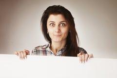 Mujer atractiva que mira a escondidas detrás de un whiteboard Fotos de archivo libres de regalías