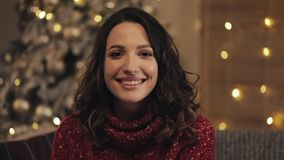 Mujer atractiva que mira y smilling en la cámara en fondo del árbol de navidad Cámara lenta almacen de video