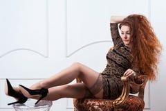 Mujer atractiva que muestra sus piernas en las medias femeninas que se sientan en silla Imagenes de archivo