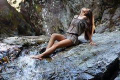 Mujer atractiva que pone cerca de una cascada Imagenes de archivo