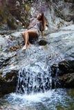 Mujer atractiva que pone cerca de una cascada Fotos de archivo libres de regalías