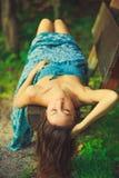 Mujer atractiva que pone en el banco en el bosque Imagenes de archivo
