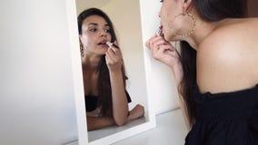 Mujer atractiva que pone en la barra de labios en el espejo metrajes