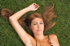 Mujer atractiva que pone en la hierba Imagen de archivo
