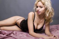 Mujer atractiva que pone en la manta púrpura Fotografía de archivo libre de regalías