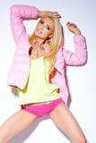 Mujer atractiva que presenta en chaqueta y pantalones cortos rosados Foto de archivo