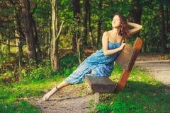 Mujer atractiva que presenta en el banco en el bosque Imagen de archivo